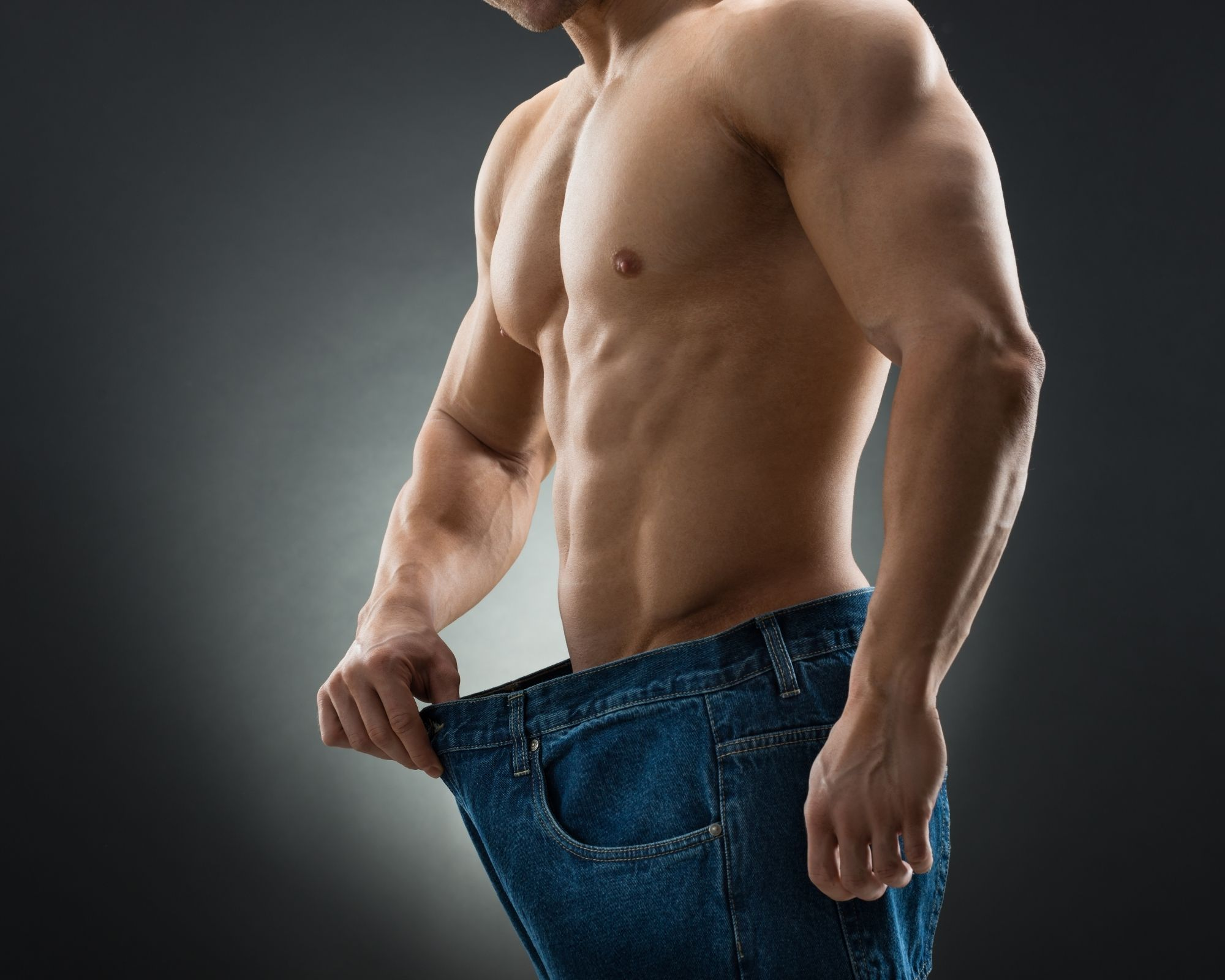 Man in old jeans showing weight loss