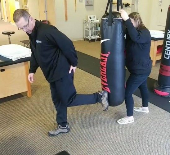 Man demonstrating the donkey kick on a punching bag - Perfect stance - Key word Heal
