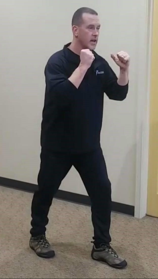 Male positioned with left foot behind him in a fighting stance - demonstrating first part of the movement for to strengthen the muscles