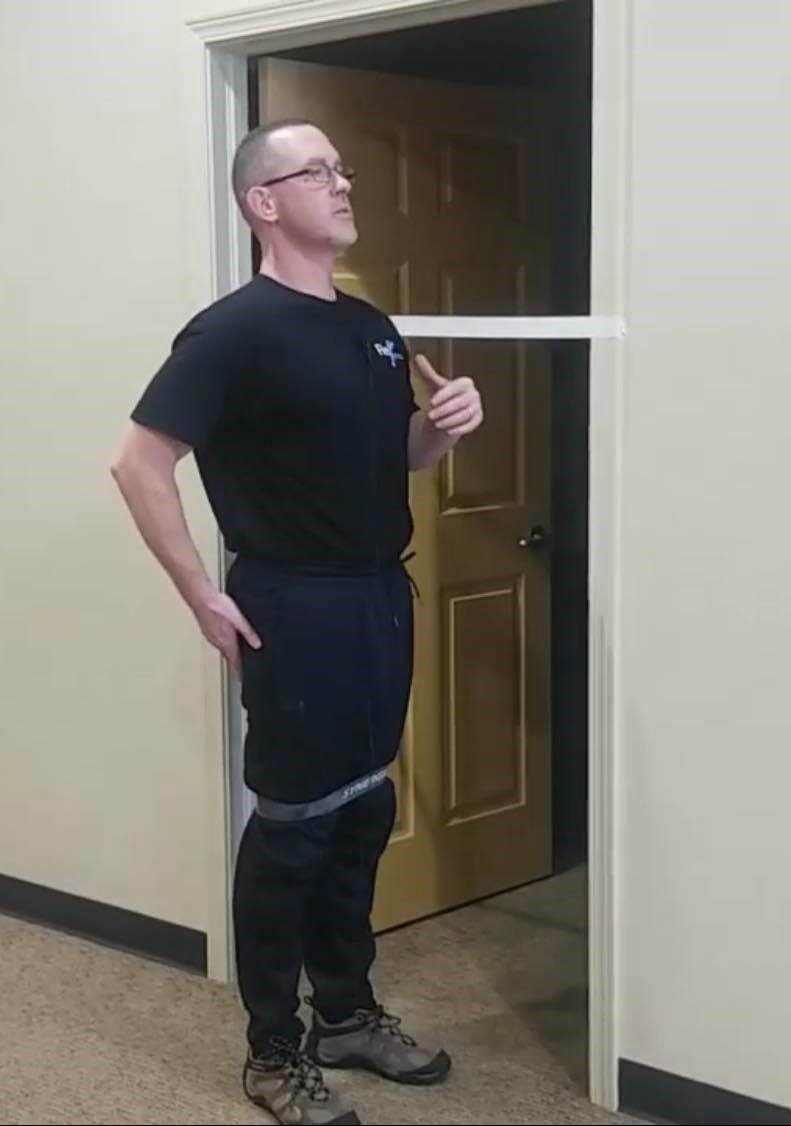 Man standing next to door frame with tape - Showing Example of the movement.