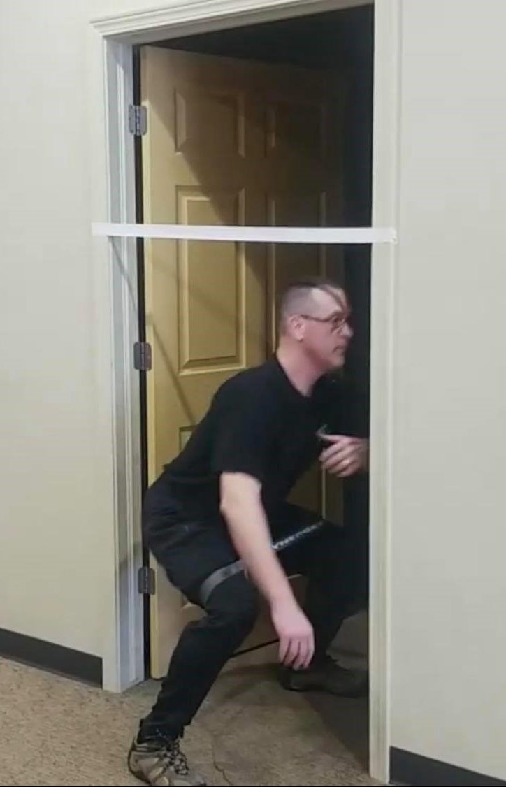 Man ducking under the tape in the door frame - Showing Example of the movement.