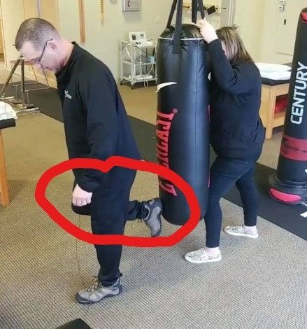 Man demonstrating the donkey kick on a punching bag - but too close to the bag. - Key word Heal
