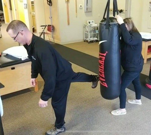 Man demonstrating the donkey kick on a punching bag - but too far away from the bag. - Key word Heal