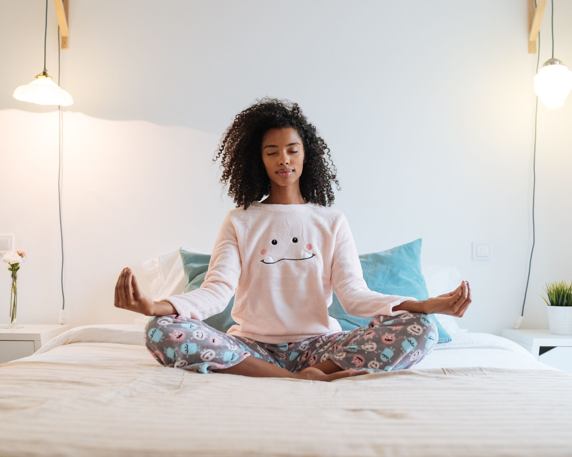 Woman meditating on her bed.