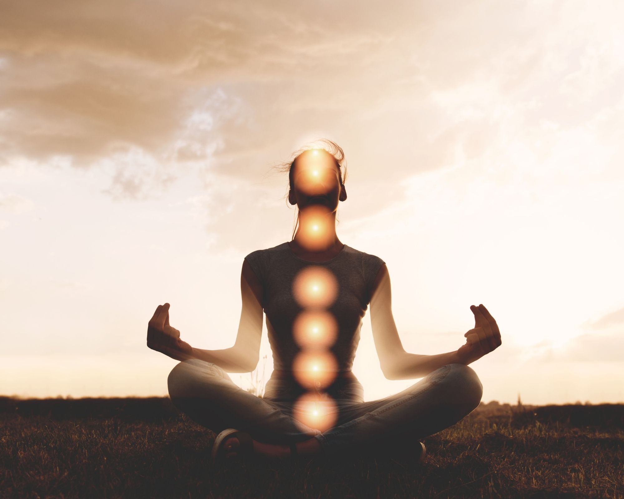 Person meditating with the chakras highlighted.