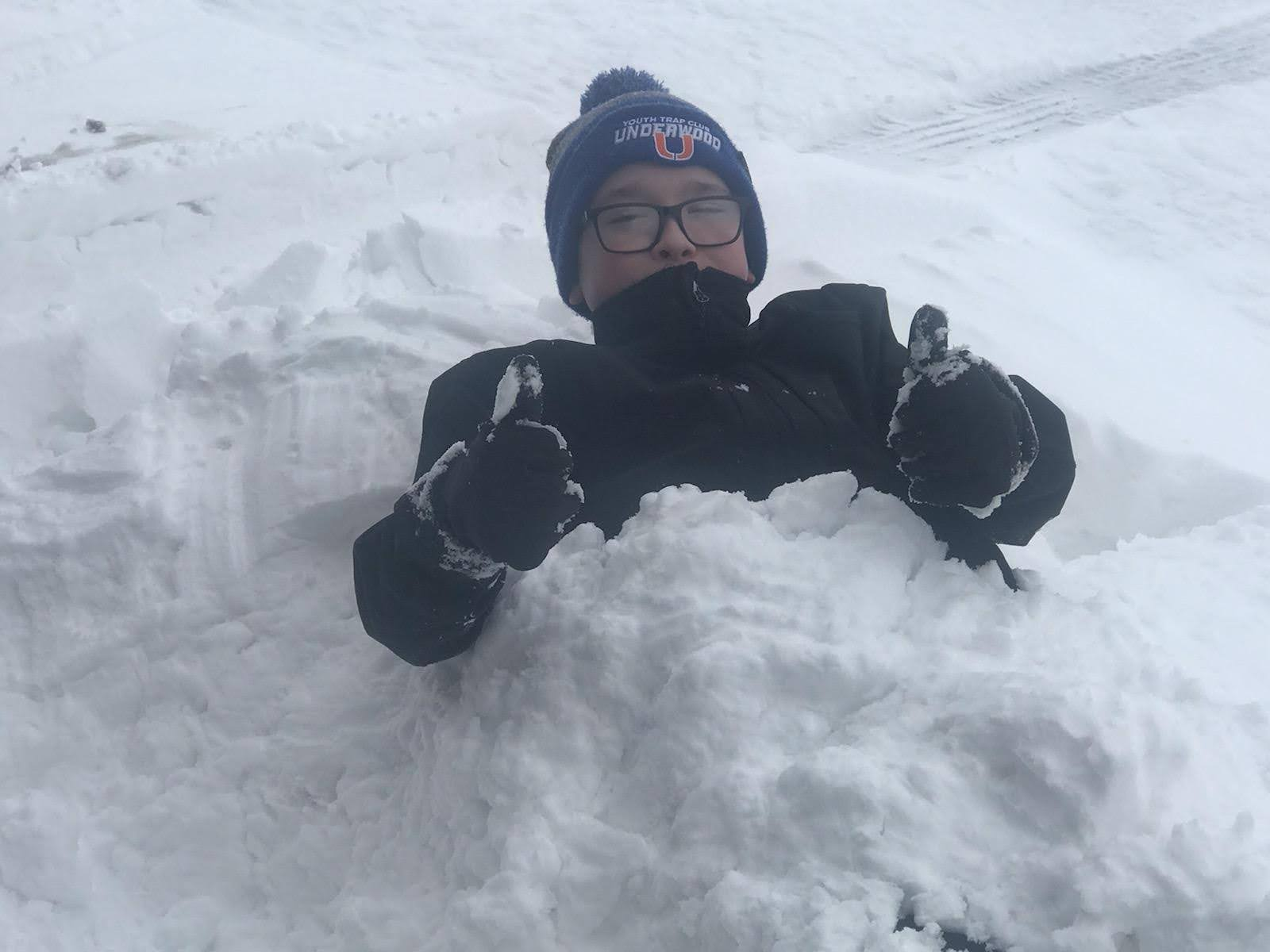 Boy holding thumbs up burried in snow. - energy