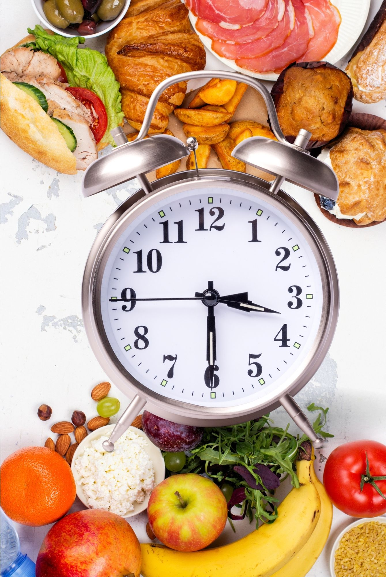 A clock placed in etween food to represent Intermittent Fasting