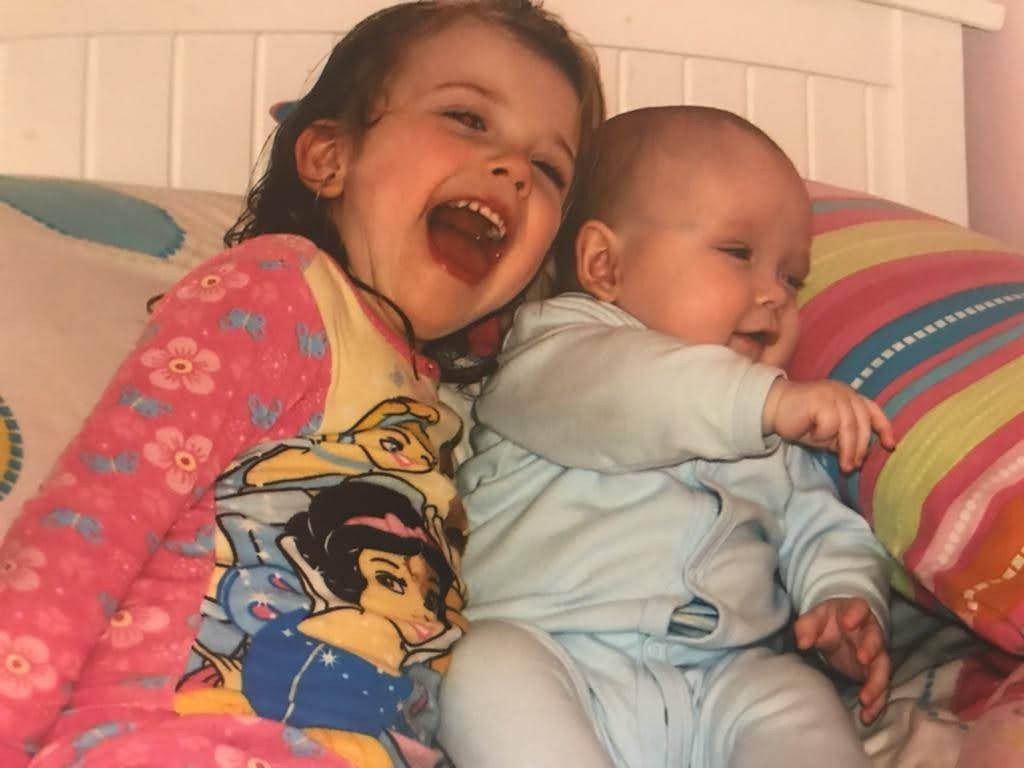 Younger Kaia with her baby brother Garrett on the couch