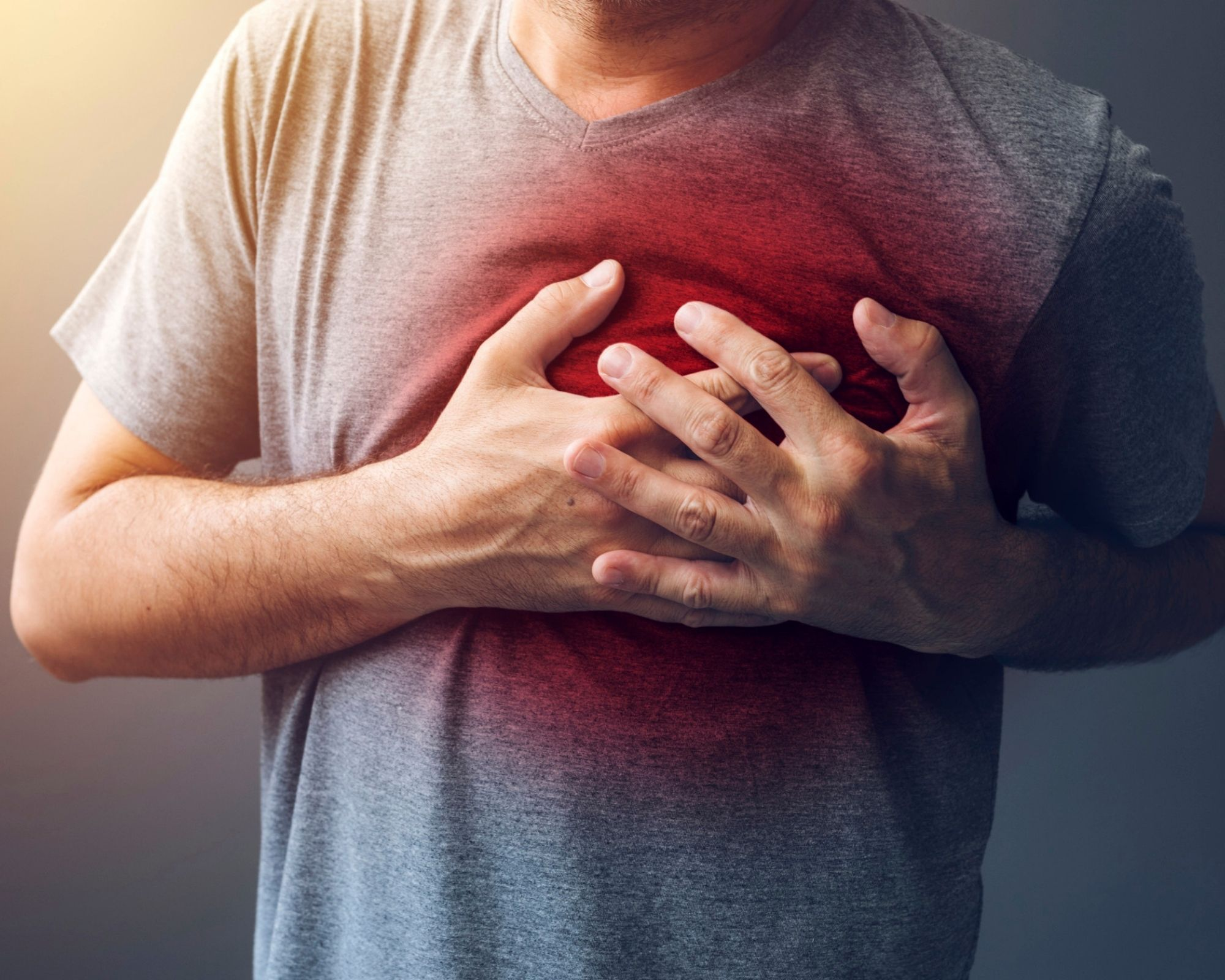 Man holding his chest over his heart with red - indicating a heart attack - could have been prevented with olive leaf extract