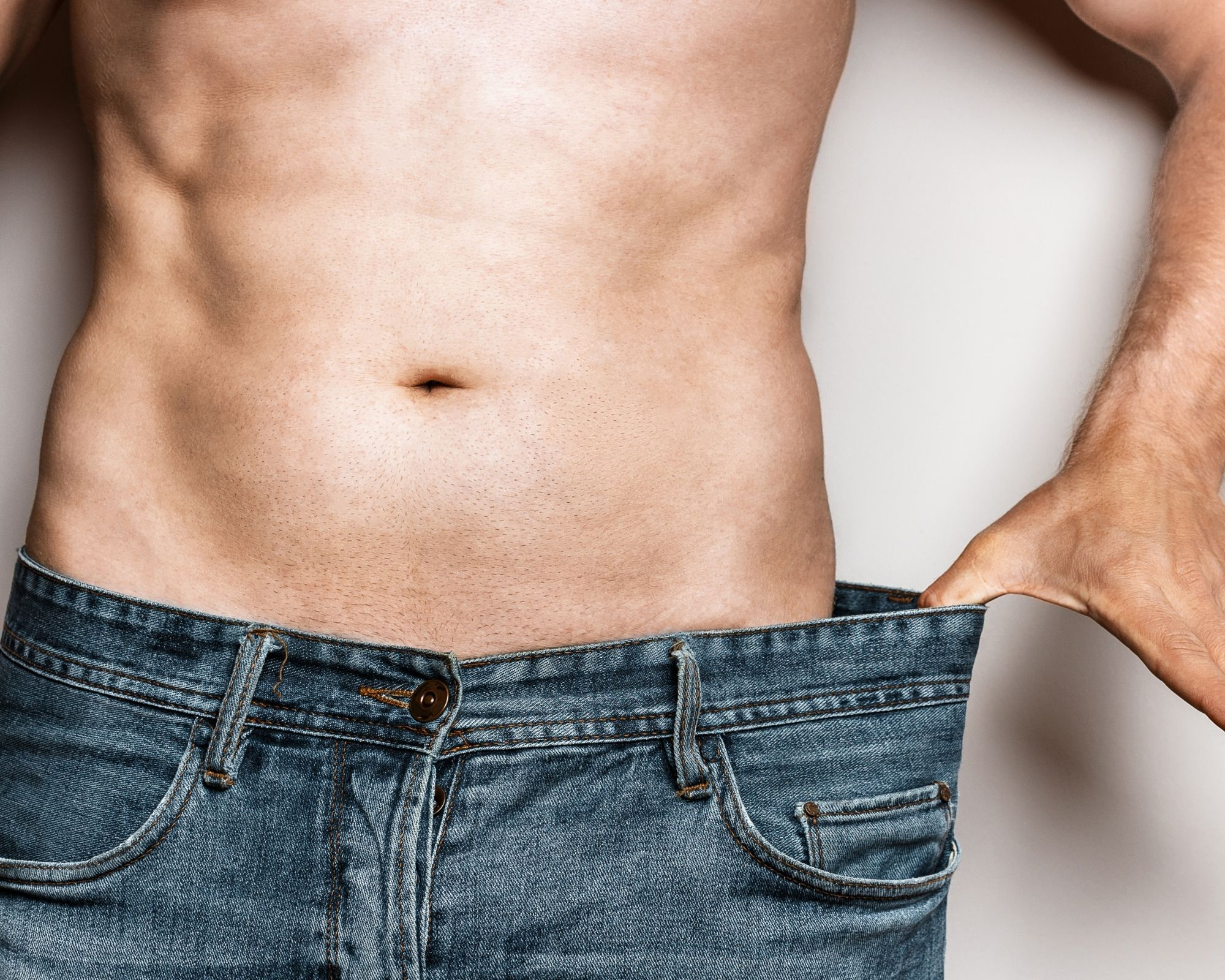 Man holding out pants to show weight loss from healthy nutrients